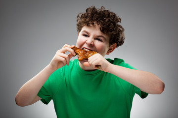 Boy eating roasted chicken leg