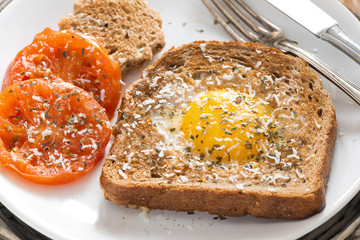fried egg and tomatoes in a toast for breakfast, close-up