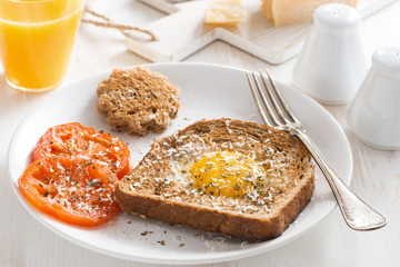 fried egg in a toast and grilled tomatoes