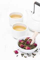 green tea with rosebuds in a bowl, cups and teapot, vertical
