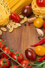 pasta, spices and cherry tomatoes on a wooden board