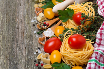 pasta, tomatoes and spices on wooden background, horizontal