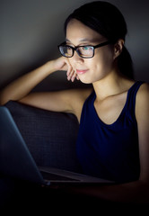 Woman watch something on computer at night