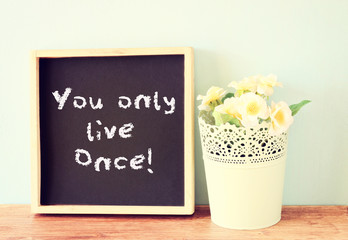 blackboard with the phrase you only live once written on it. con