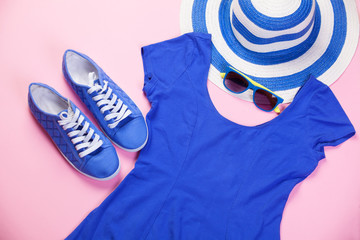 Gumshoes, sunglasses and dress on pink background.