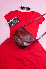 Camera, bag, dress and sunglasses on pink background.