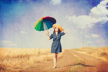 Brunette girl  with umbrella on country side road.