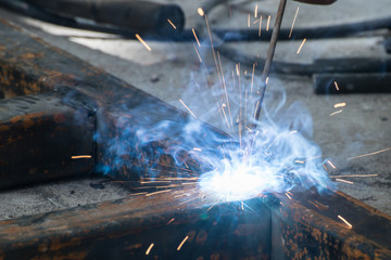 Worker welding steel with sparks lighting