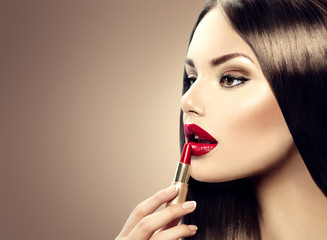 Professional make-up. Lipgloss. Beauty girl applying lipstick