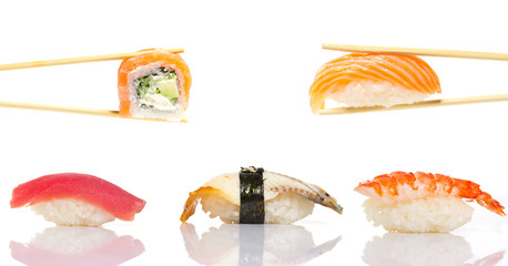 Sushi roll and nigiri in chopsticks isolated