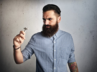Portrait of brutal bearded man looking at vintage razor