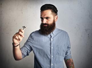 Portrait of brutal bearded man looking at vintage razor