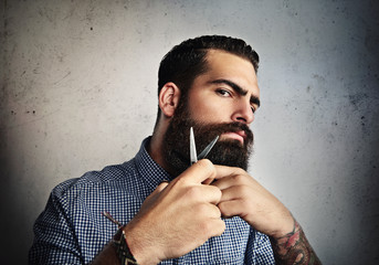 Portrait of a man grooming his beard with scissors