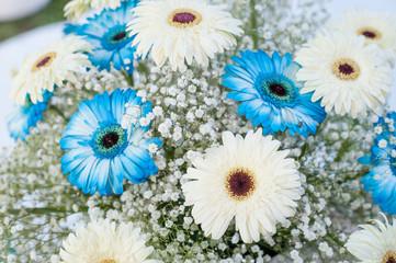 particolare di bouquet di gerbere bianche e azzurre e mughetti