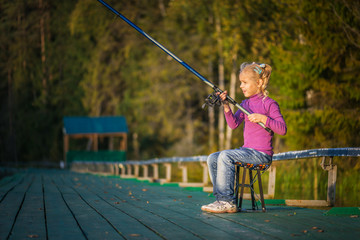 little girl catches fishing rod