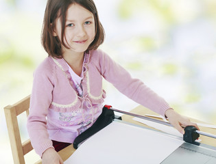 girl cutting paper roller cutter.