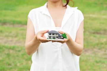 家の模型を紹介している女性の上半身