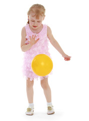 little girl tosses the ball