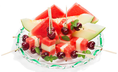 Mixed fruit salad ( watermelon, melon, cherry, mint ) in the dis