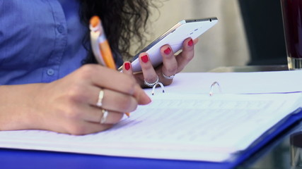 Businesswoman hands working with smartphone and documents