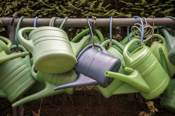 some old watering cans on a rusty pipe