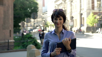 Happy attractive businesswoman with tablet computer in city