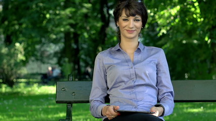 Happy attractive businesswoman with tablet computer in the park
