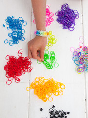 childs hand and coloured elastic bands