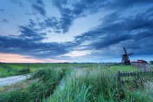 wiatrak na łące na wschód słońca