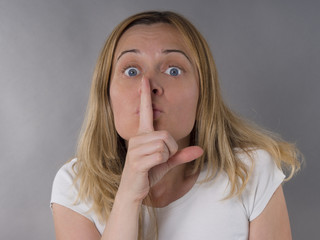 blonde woman with finger on her lips, silence