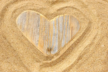 Single wooden love heart in the sand