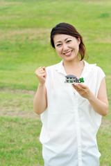住宅の模型を持っている白い服の女性