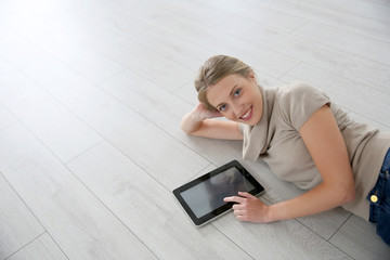 Smiling woman laying on wooden floor with tablet