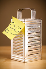 Post-it note with smiley face sticked on a grater