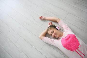 Blond girl relaxing on wooden flooring with headphones on