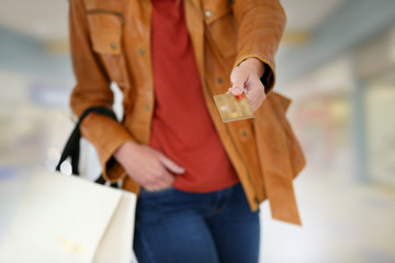Closeup of credit card held by shopping girl