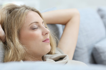 Blond woman in sofa relaxing with eyes shut