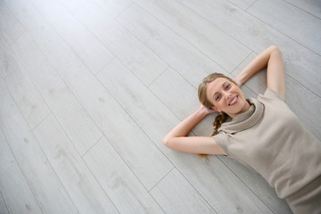 Upper view of smiling woman relaxing laid on floor
