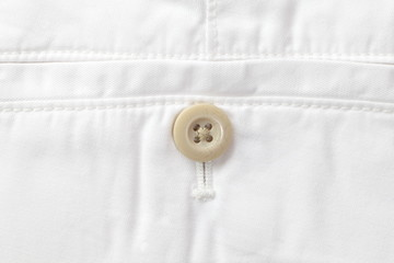 Close - up button and white short pants