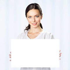 Businesswoman showing blank signboard, at office