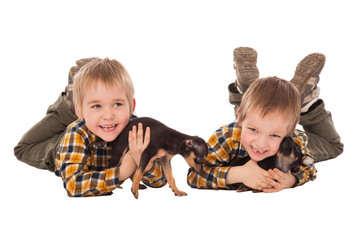 smiling boys hodling puppies lie on the floor