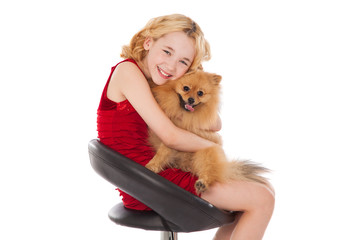 beautiful blonde little girl holding  her dog wearing red dress