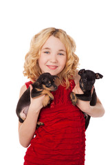 blonde little girl holding two puppies wearing red dress