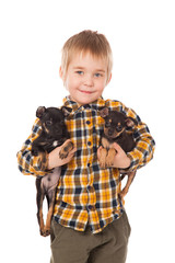 smiling little boy holding his puppies