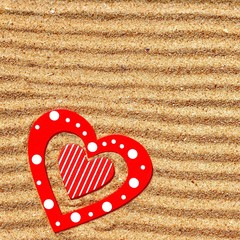 Two wooden love heart in the sea sand