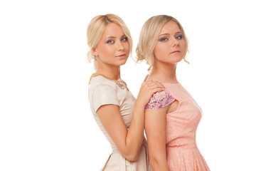 Two beautiful girls in fashion dresses isolated