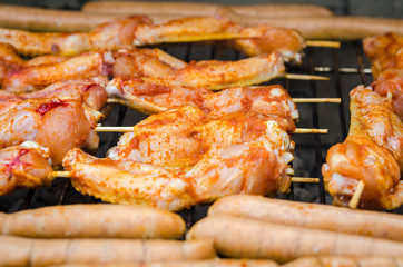 Sausages and chicken wings on smoking grill barbeque