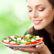 Portrait of happy smiling woman with plate of salad