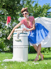 woman doing laundry with vintage wringer washing machine