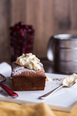 chocolate cake with cream cheese, raw cherry on white plate